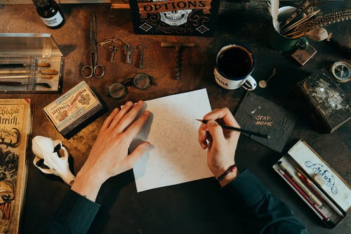 Person Writing on White Paper Beside Black Ceramic Mug