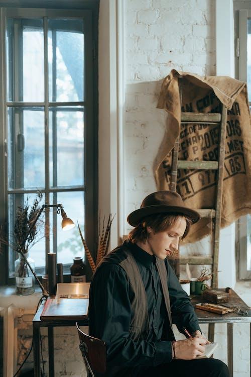 Woman in Black Leather Jacket Wearing Brown Fedora Hat Standing Near Window