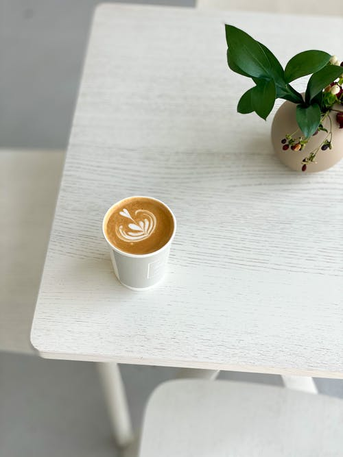 White Ceramic Cup With Cappuccino on White Wooden Table