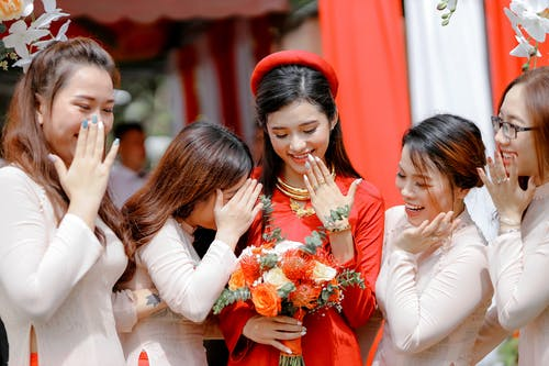 Happy Asian bride and guests on party