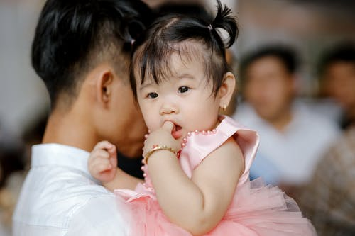 Adorable Asian toddler with ponytails in pink dress sitting on hands and sucking finger