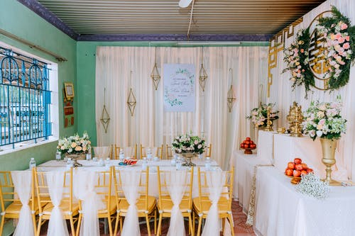 Decorated room with banquet table and huge number of flowers for wedding celebration in daylight