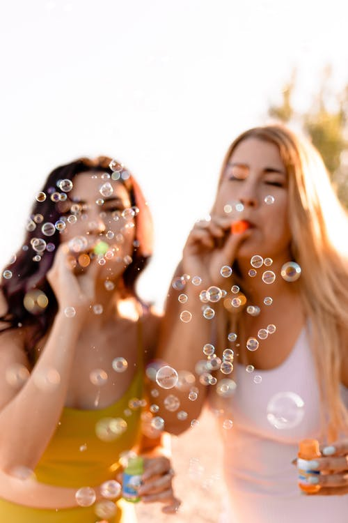 Cheerful sisters blowing bubbles in park