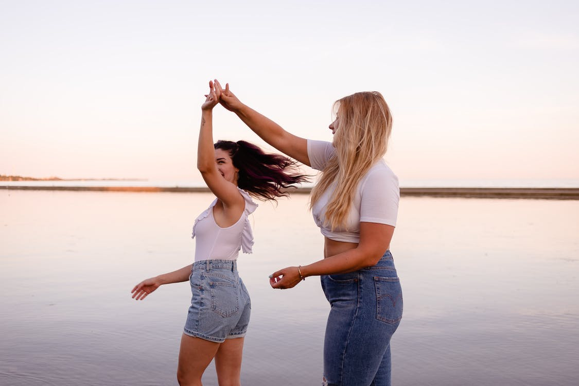Side view of young smiling women dancing and having fun together on coastline in sunset