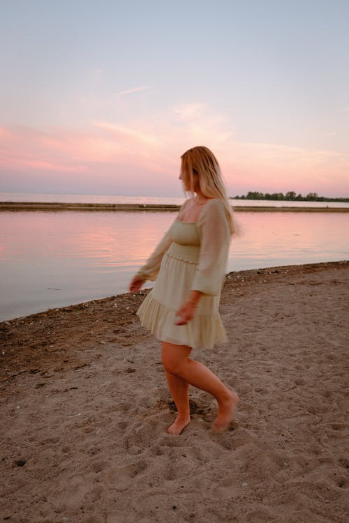 Woman in White Long Sleeve Dress Standing on Beach