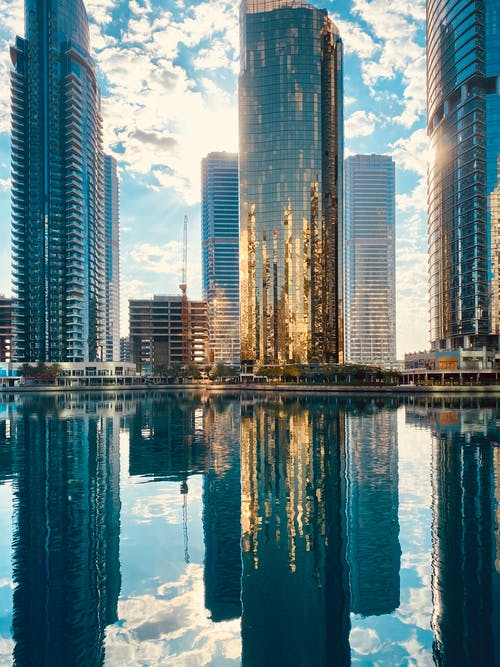 Modern city district with skyscrapers reflecting in pond