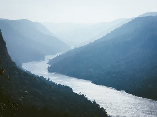 Scenic view of rippled river between ridges with trees under light sky on misty day