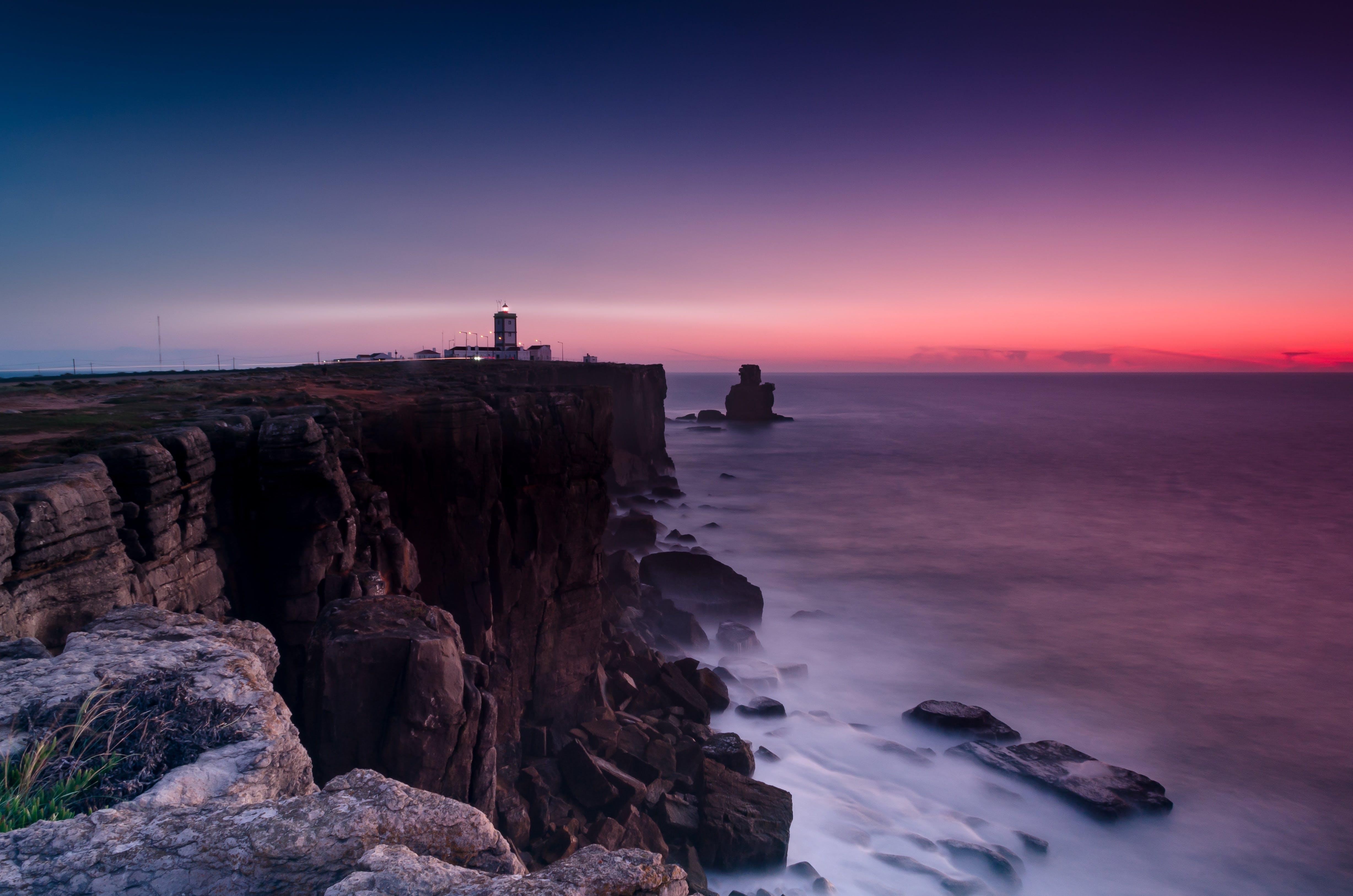 Scenic View Of Ocean Near Cliffs During Dawn