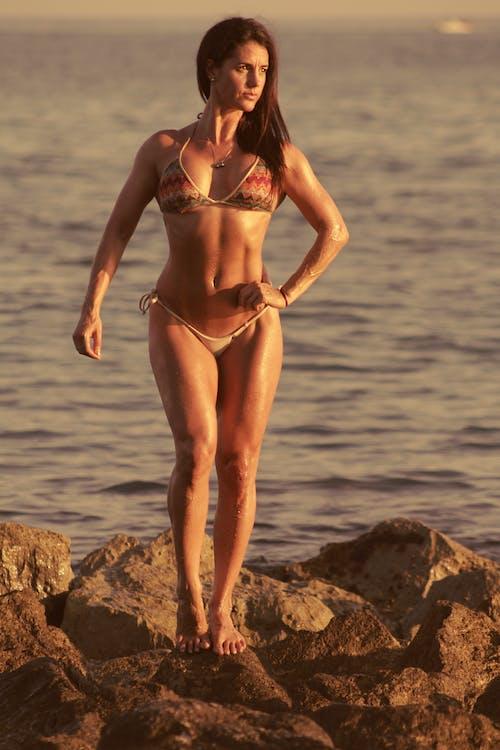 A Sexy Woman in Bikini Posing on the Rocks near the Sea