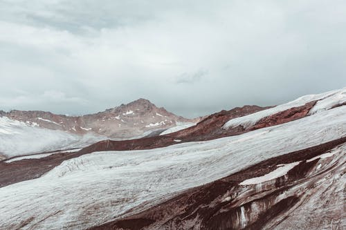 Snowy mountain slope under cloudy sky