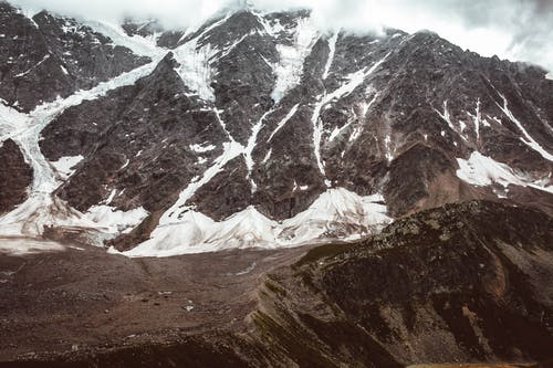 Snowy mountain ridge under cloudy sky