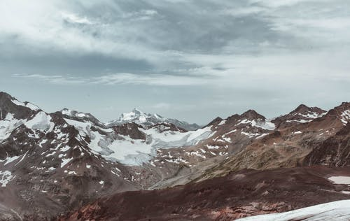 Majestic scenery of rough mountain peaks in snow and ice in cold cloudy weather