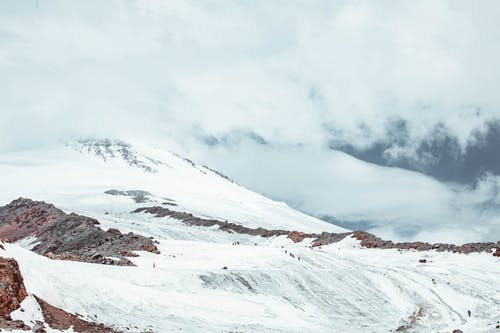 Picturesque view of snowy mountain peak with icy slope on height in daylight