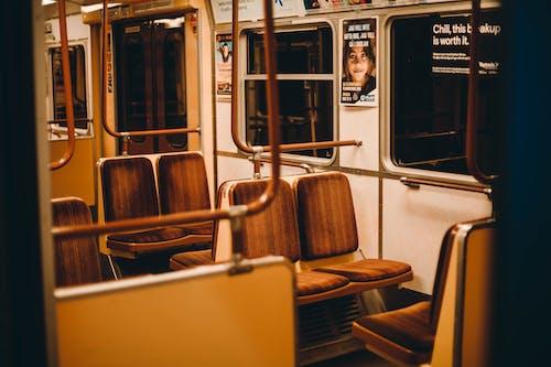 Interior of empty subway train with metal railing and seats near big windows