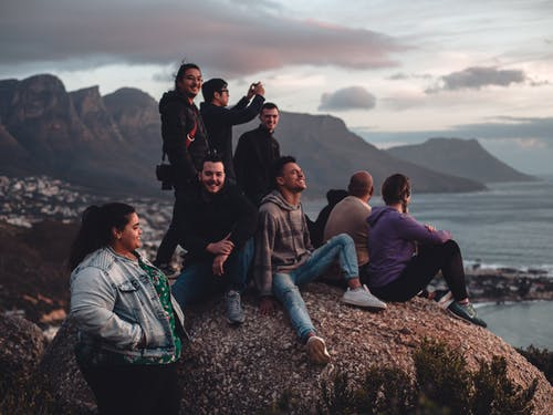 Group of People Sitting on Brown Rock Mountain