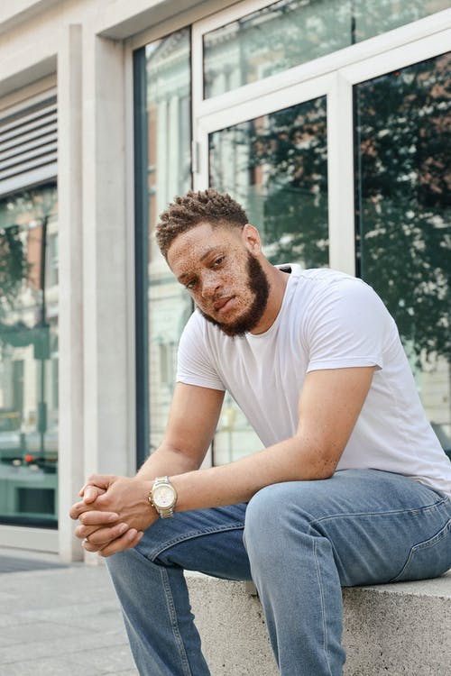 Man in White Crew Neck T-shirt and Blue Denim Jeans Sitting on White Wooden Window