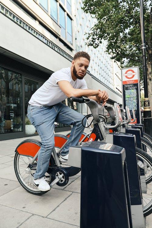 Man in White T-shirt Riding on Black and Orange Bicycle