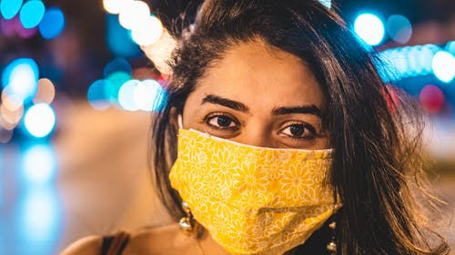 Woman Wearing a Yellow Face Mask With Flowers