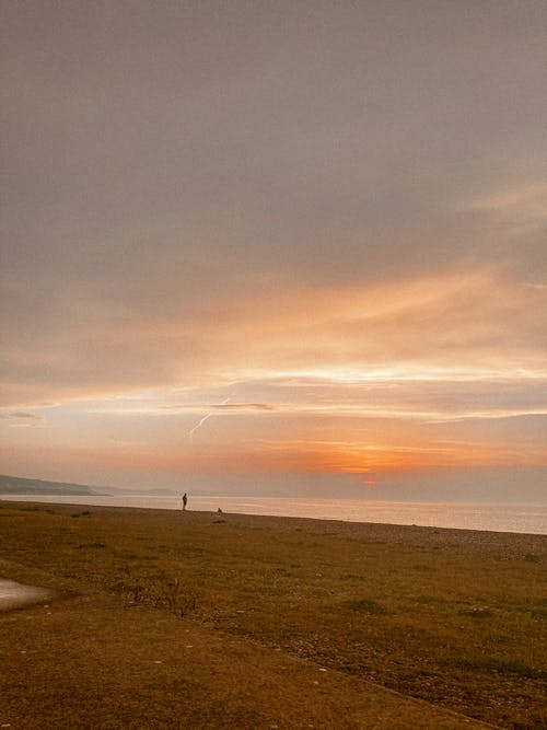 Picturesque scenery of lonely sandy beach near calm sea water under colorful sky at sundown