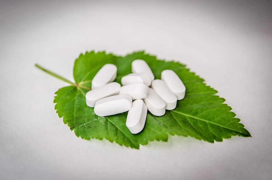White Oval Medication Pill on Green Leaf