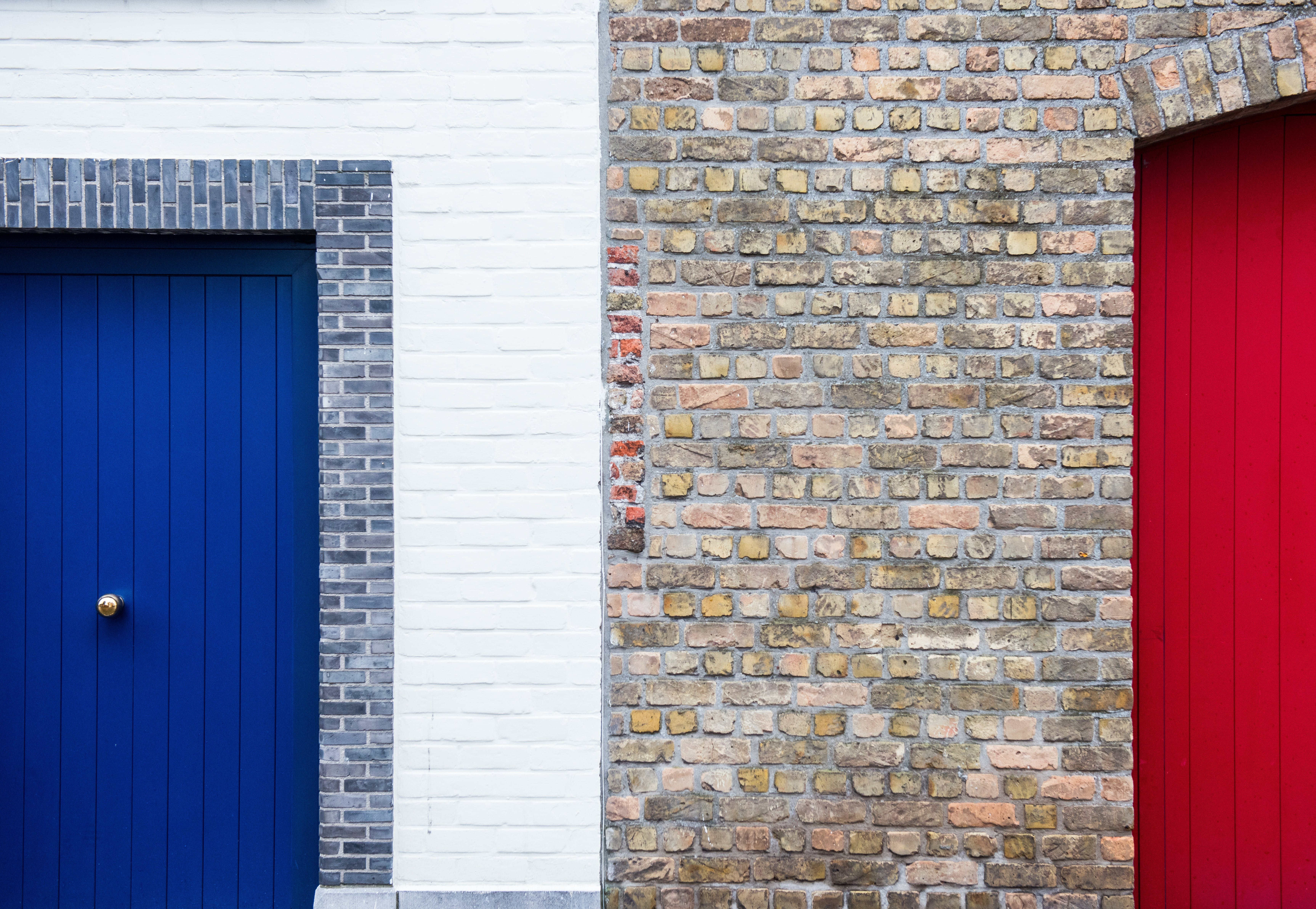 Bricked Wall in Between of Red and Blue Painted Door during Daytime