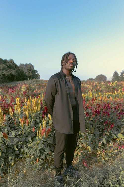 Cheerful black man standing in field
