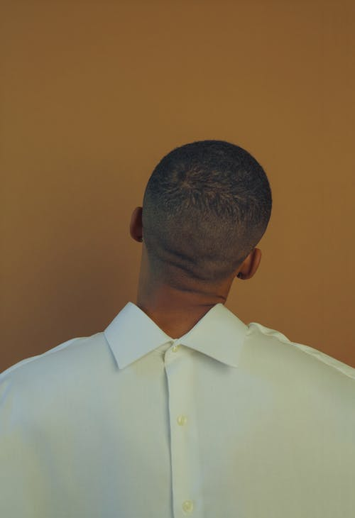 Back view of African American male with short hair wearing white clothes and posing in front of beige background