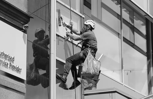 Male worker washing glass facade of building