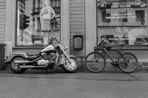 Black and white of cool motorbike and old fashioned cycle placed near store shop on pavement