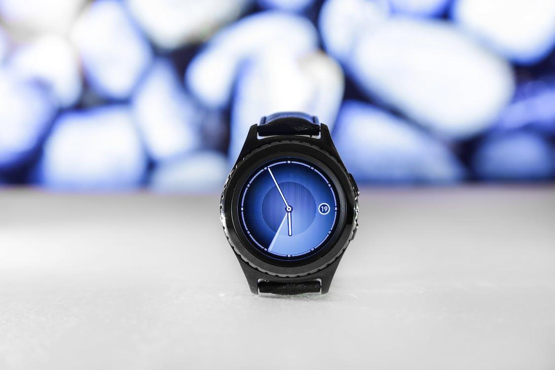 Black Samsung Gear Displaying 05:55 on White Surface