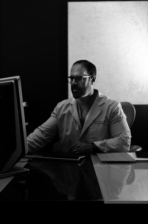Man in Dress Shirt Wearing Sunglasses in Front of Computer