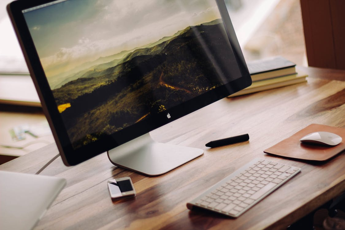 Flat Screen Monitor Beside White Iphone