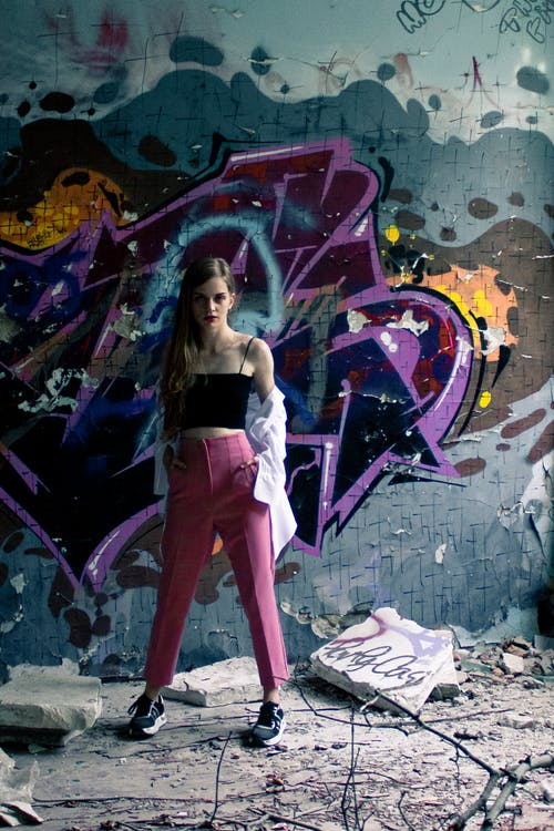 A Woman Posing in Front of a Graffiti Wall