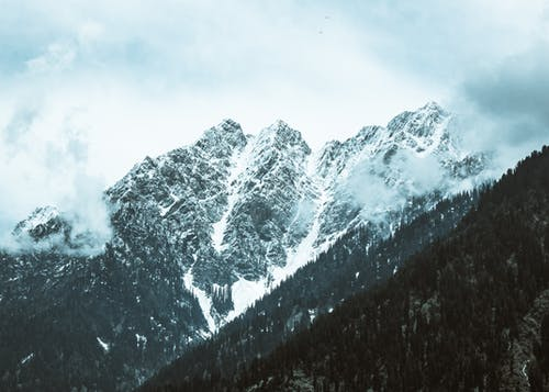 Spectacular view of rough mount with snow against trees under sky with clouds in foggy weather