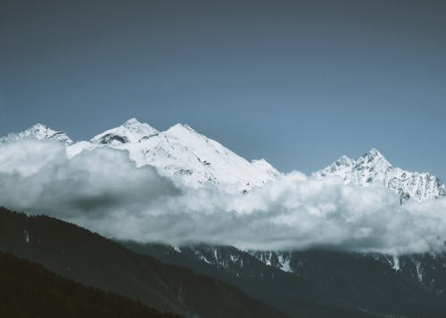 Snowy mountain peaks covered with clouds
