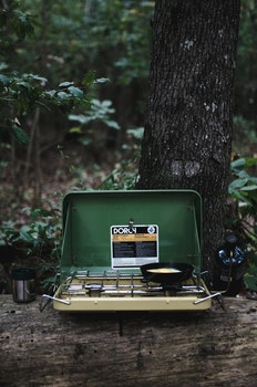 Dorcy Portable Stove on Log Near Tree With Green Grass and Trees during Daytime