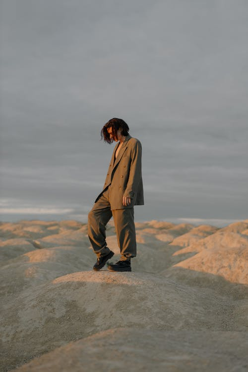 Man in Brown Coat Standing on Rock Formation