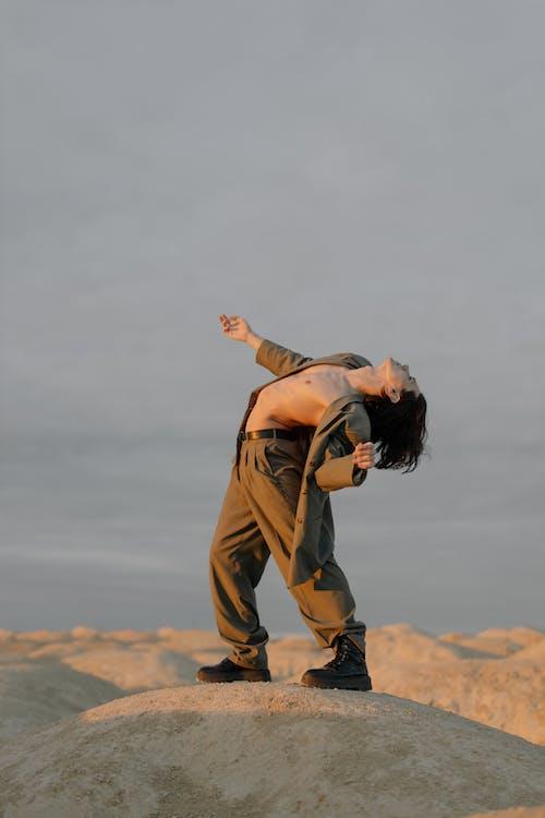 Woman in Brown Long Sleeve Shirt and Brown Pants Standing on Brown Field