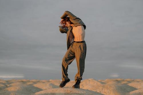 Man in Brown Jacket and Brown Pants Standing on Brown Rock