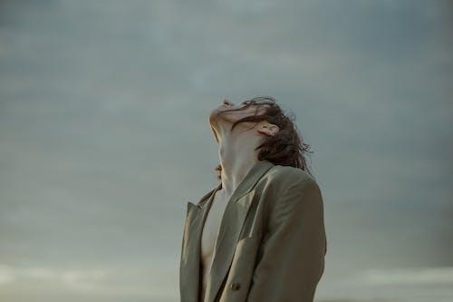 Woman in Beige Coat Standing Under White Sky