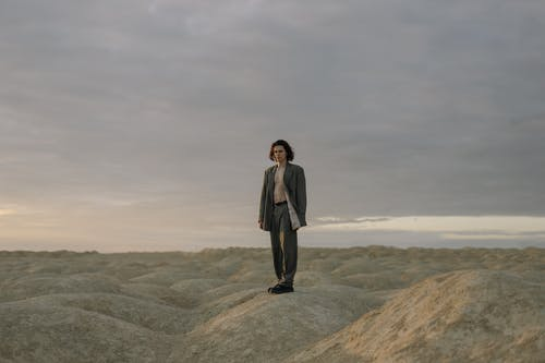 Man in Black Suit Standing on Brown Rock Formation