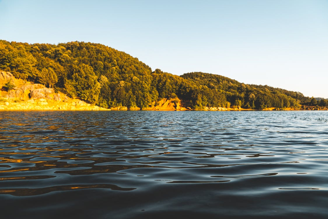 Green and Brown Mountain Beside Body of Water