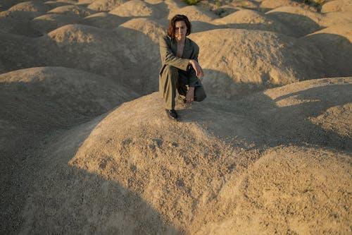 Woman in Brown Jacket Sitting on Brown Rock