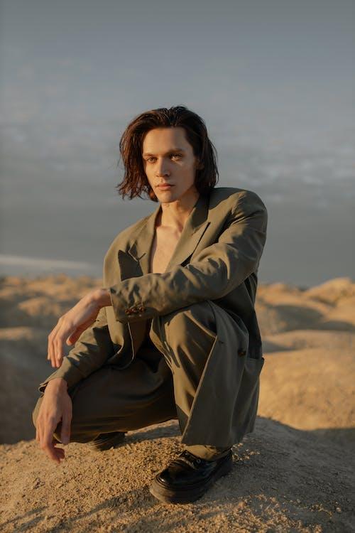 Woman in Brown Coat Sitting on Brown Rock