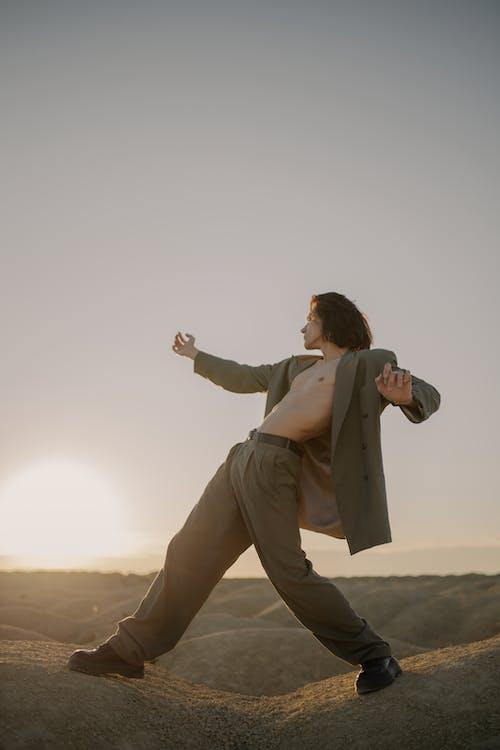 Man in Brown Pants and Brown Jacket Standing on Brown Field