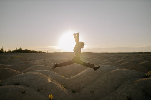 Woman in White Shirt and Black Shorts Jumping on Brown Sand