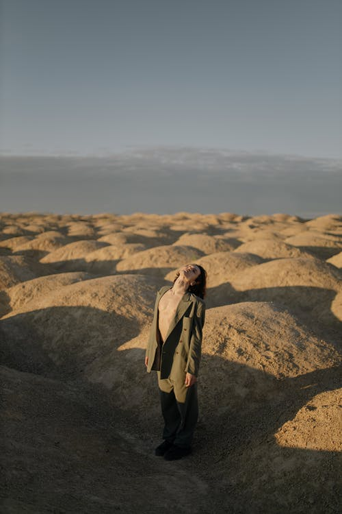 Woman in Brown Coat Standing on Brown Rock Formation