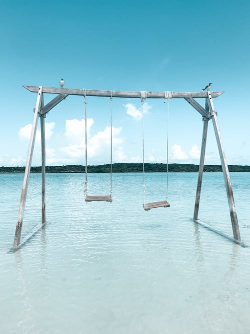 Brown Wooden Swing on White Sand