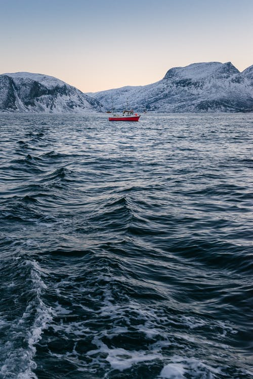 Red Boat Anchored at the Bay Near Snow Covered Mountain