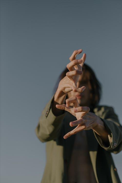 Person in Brown Coat Raising Both Hands